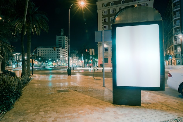 Blank advertisement on footpath with blurred traffic lights at night