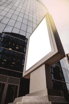 Пустой рекламный щит перед зданием бизнеса. баннер на фоне небоскреба выполнен в современном стиле. архитектура здания в деловом районе мегаполиса. авторские права
