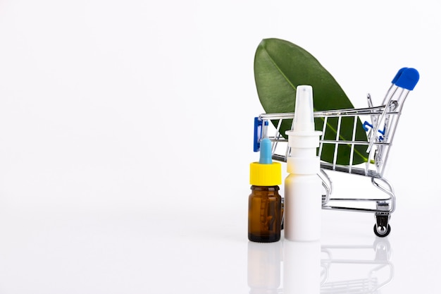 ピペット、緑の葉の背景に点鼻薬と空白の琥珀色のガラスのエッセンシャルオイルボトル。