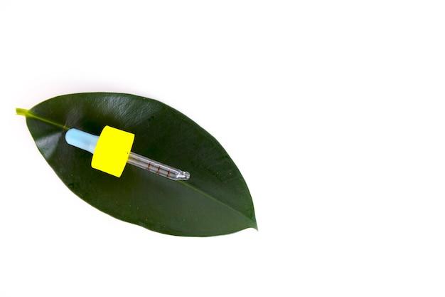 緑の葉の背景にピペットで空白の琥珀色のガラスのエッセンシャルオイルボトル。コピースペース