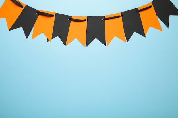 青い背景の上のハロウィーンの装飾のための空白とオレンジ色のパーティーフラグ