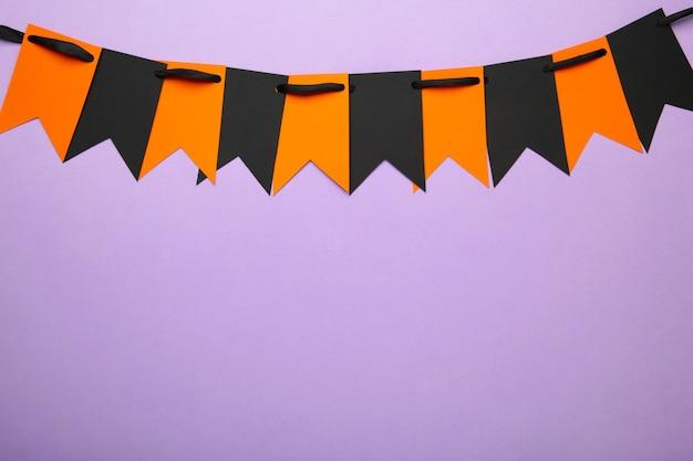 紫の背景にハロウィーンの装飾のための空白とオレンジ色のパーティーフラグ。上面図