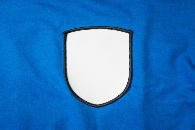 Blank arm patch on blue sport shirt. white team logo and emblem for your montage or edit.