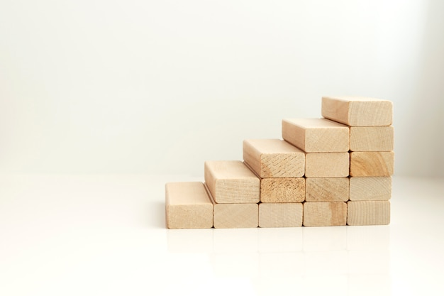 Blank arranging wooden block stacking as step stair on whith background. business concept for growth success process. copy space
