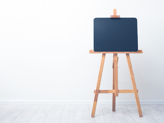 Blank art blackboard, wooden easel, front view, against the background of a white wall.
