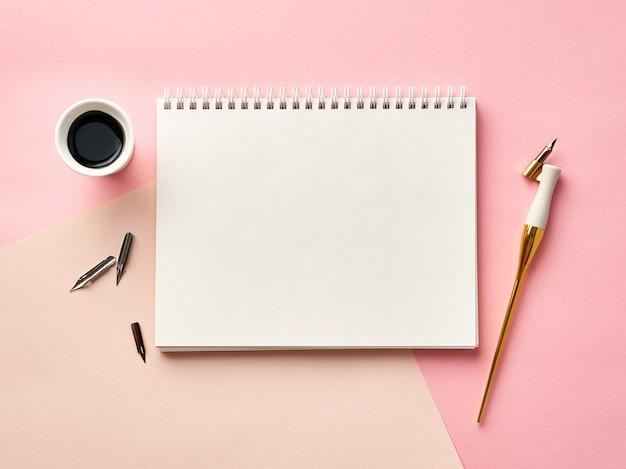 書道ペンとインクとピンクの背景の空白のアーティストスケッチブック。上からの眺め。