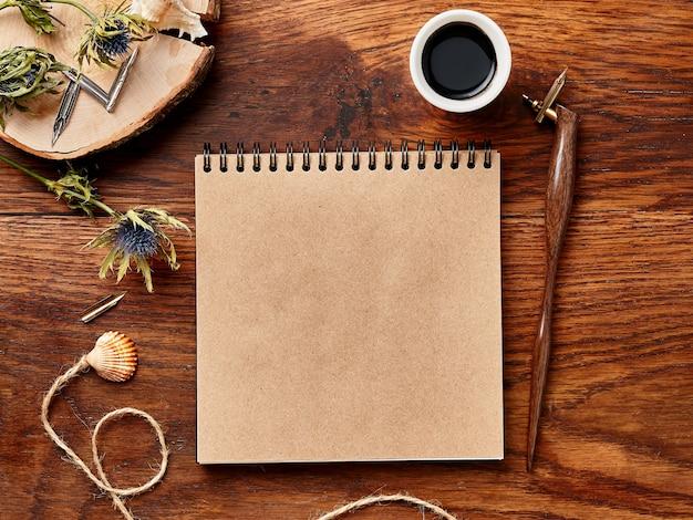 書道ペンとインクで木製の背景の空白のアーティストスケッチブック。上からの眺め。