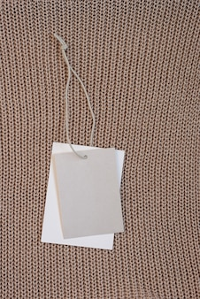 Blank beige clothes tag label mockup on knitted textile surface