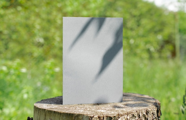 Blank bifold white card standing on wooden desk outdoor with floral shadow and blurred nature background