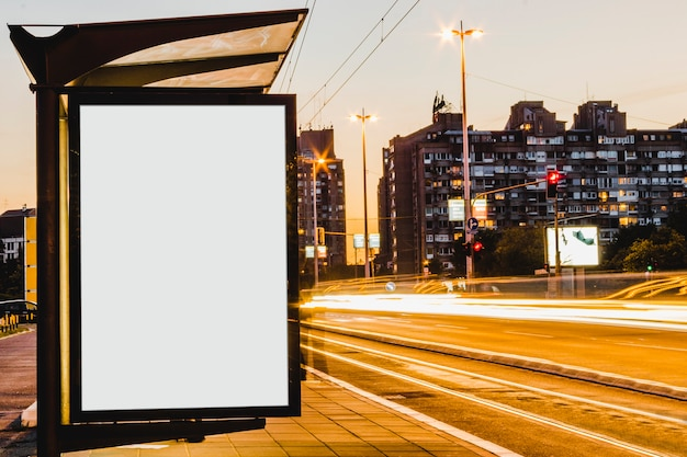 Blank billboard in bus stop at night with the lights of the cars passing by