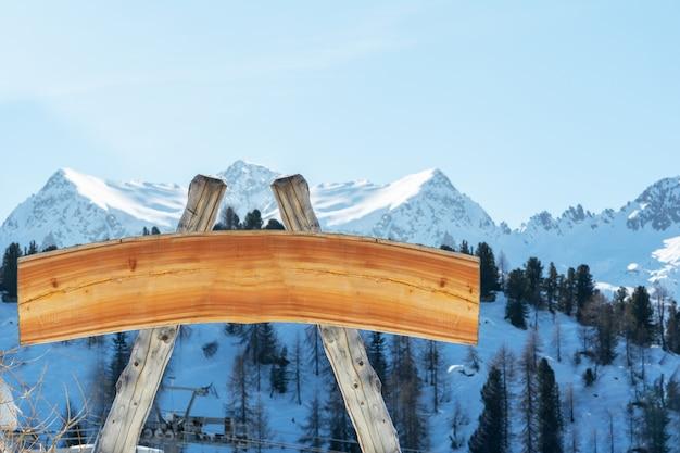 Пустой рекламный щит для наружной рекламы из бревен и деревянная доска на горнолыжном склоне на фоне гор. концепция рекламы, пейзаж, спорт.