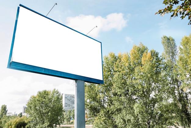 Blank billboard near green trees