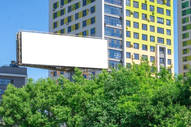 建物と緑の木々の背景にブランクの看板。モックアップ