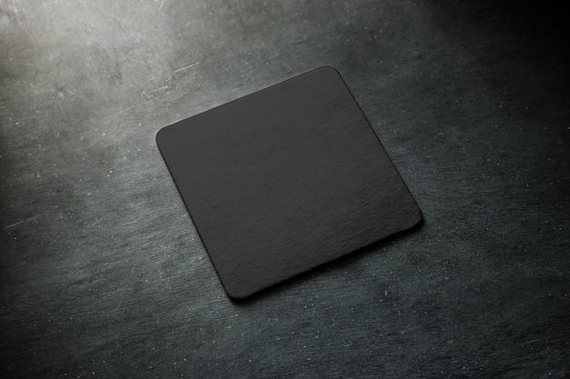 Blank black beer coaster  lying on grey desk