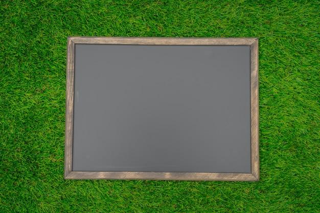 Пустой черный доска на траве поля