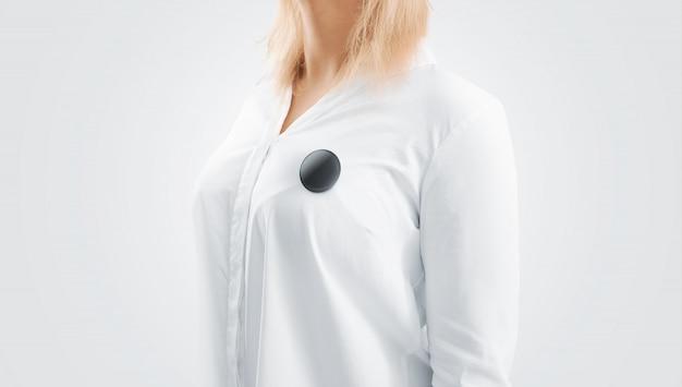 女性の胸に固定された空白の黒いボタンバッジモックアップ
