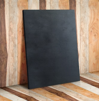 Blank black canvas on wooden plank wall and floor