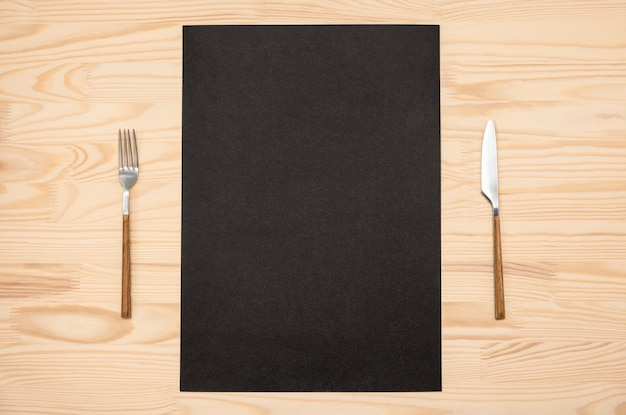 Blank black card a4, a3 and cutlery on wooden table. top view black recipe paper page
