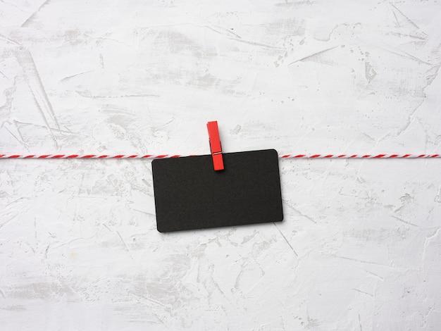 종이의 빈 검은 골판지 직사각형 시트는 clothespins, 흰색 시멘트 벽 배경에 걸어