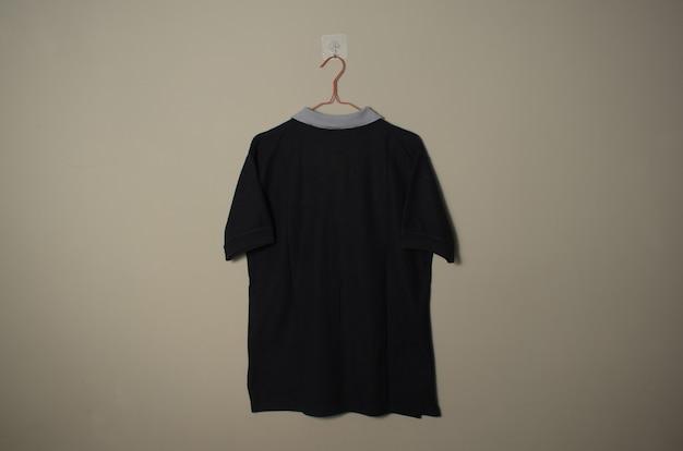 壁の背景の背面図でハンガーにグレーの襟のモックアップと空白の黒のカジュアルなtシャツ