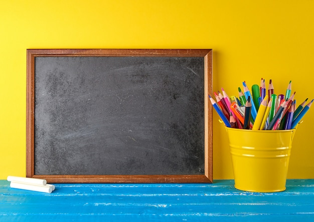 Blank black chalk frame, white chalk and school supplies