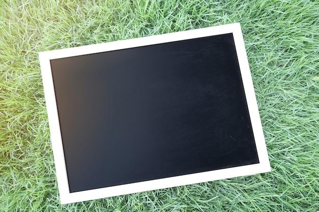 Blank black chalkboard on grass.
