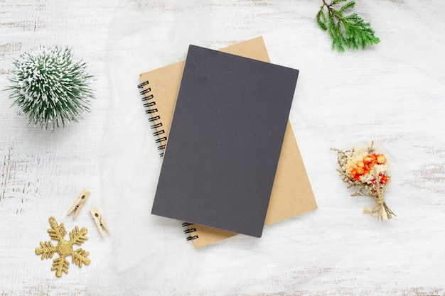Пустая черная обложка тетради и рождественские украшения на белом дереве