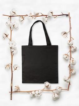 白い背景の上の綿の花の枝で作られたフレーム内の空白の黒い布バッグ
