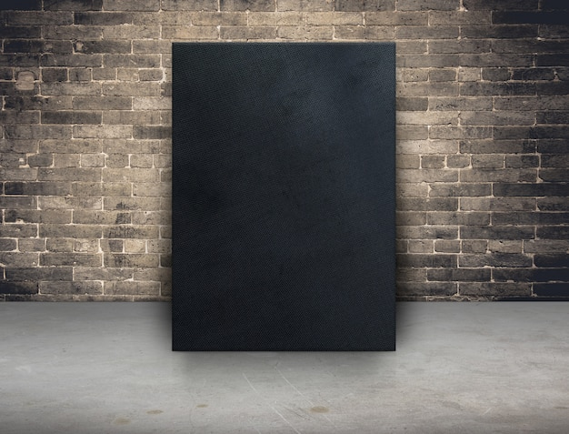 Blank black fabric canvas frame at grunge brick wall and concrete floor background