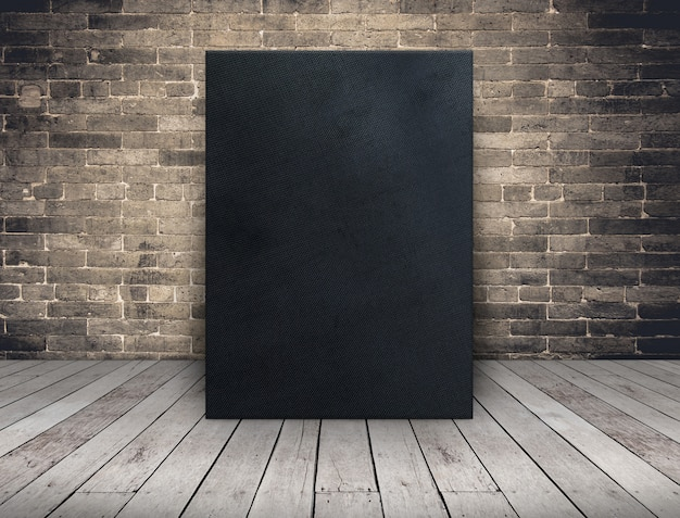 Blank black fabric canvas frame at grunge brick wall and wood plank floor
