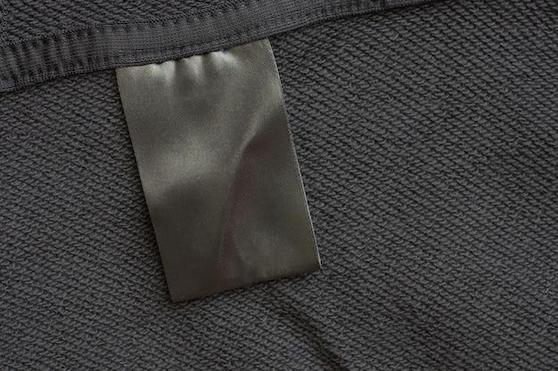 Пустая черная этикетка для одежды по уходу за стиркой на фоне текстуры черной ткани