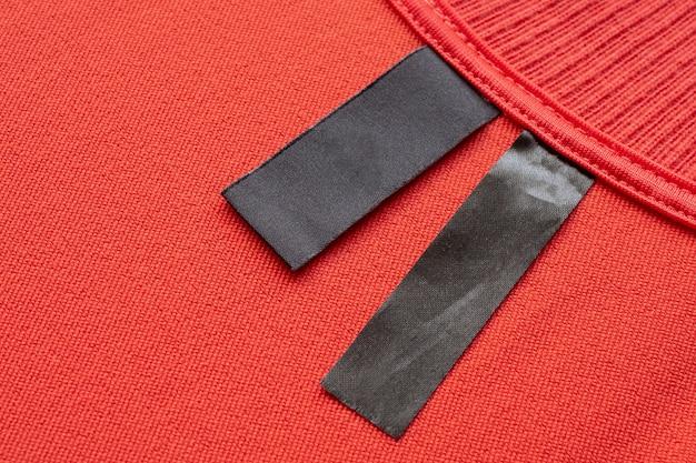 빨간색 패브릭 질감 배경에 빈 검은 세탁 관리 옷 레이블