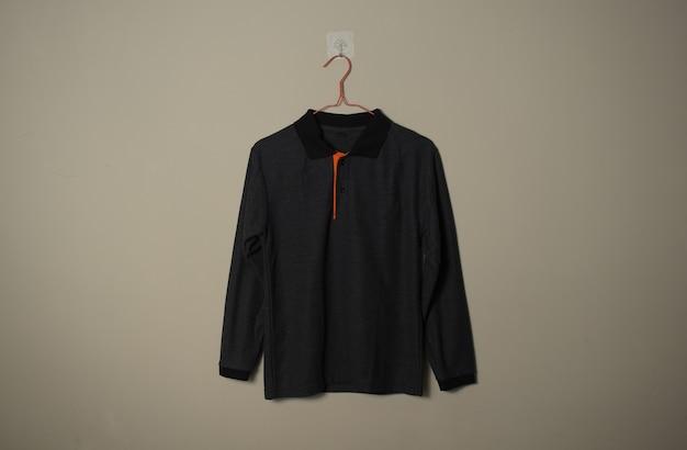 壁の背景正面側面図のハンガーに空白の黒の長袖カジュアルtシャツモックアップ