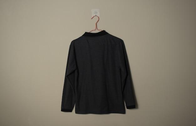壁の背景の背面図のハンガーに空白の黒の長袖カジュアルtシャツのモックアップ