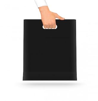 Blank black paper bag mock up holding in hand.