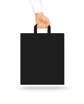 Blank black paper bag mock up holding in hand.