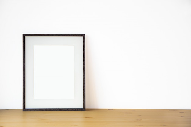 Blank black picture frame on the white wall and the wooden floor, template poster interior photo 3d background