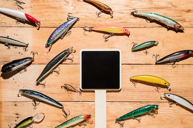 Blank black placard surrounded with colorful fishing lures on wooden desk