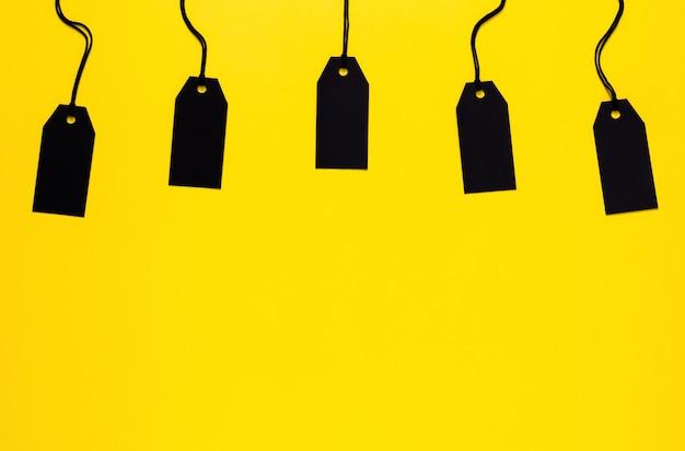 ブラックフライデーとサイバーマンデーのコンセプトの黄色の背景に空白の黒い値札。