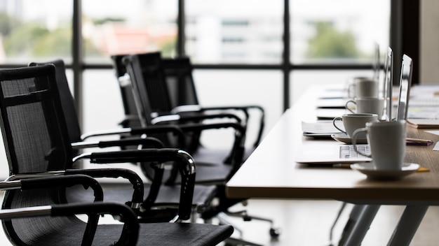 ビジネスプラングラフチャート図書類レポートターゲットドキュメントとオフィスの白いコーヒーカップでいっぱいの作業テーブル上のコピースペーステキスト用の空白の黒い画面モニターラップトップノートブックコンピューター。