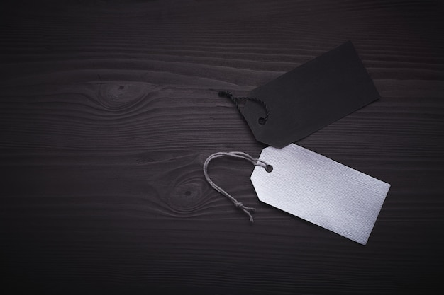 Blank black and silver tags on black wooden .