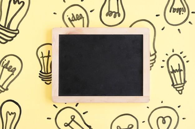 黄色の背景に電球に囲まれた空白の黒いスレート