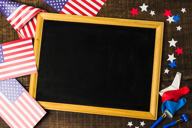 Blank black slate with american flags; stars; balloons and party blowers on wooden textured backdrop