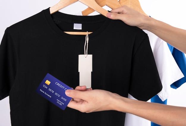 空白の黒いtシャツと広告のための空白のラベルタグ。シャツのショッピングのためのクレジットカードを持っている手。