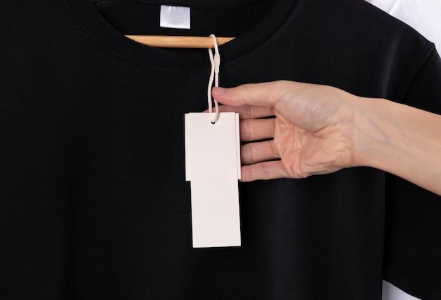 空白の黒いtシャツと広告のための空白のラベルタグ。