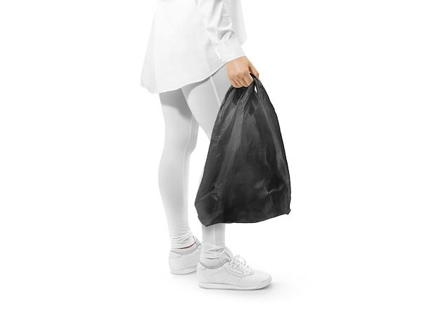 Blank black t-shirt plastic bag holding hand