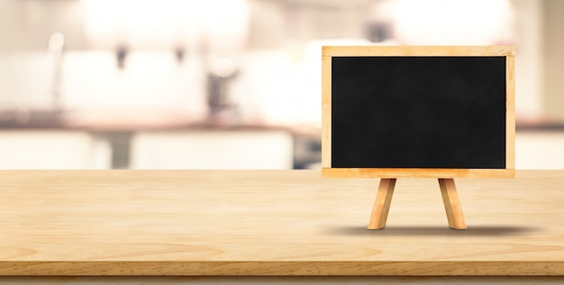 Blank blackbaord on easel on plank wooden table top with blurred home kitchen