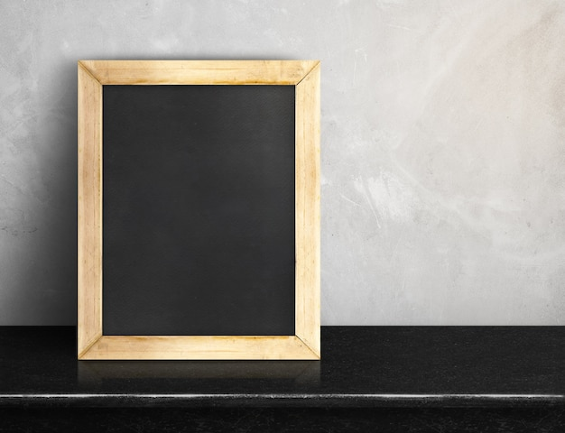 Blank blackboard on black marble table at grey concrete wall
