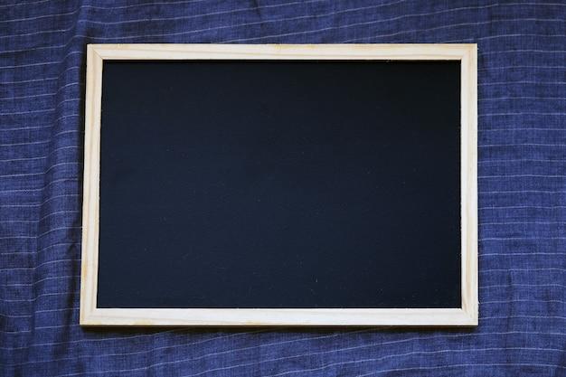 Blank blackboard on dark blue linen fabric from above