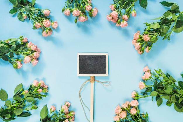 Пустой ярлык на доске в окружении розовых роз на синем фоне